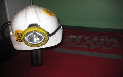 Safety helmet and headlight, with Slogan coal not dole stickers attached.